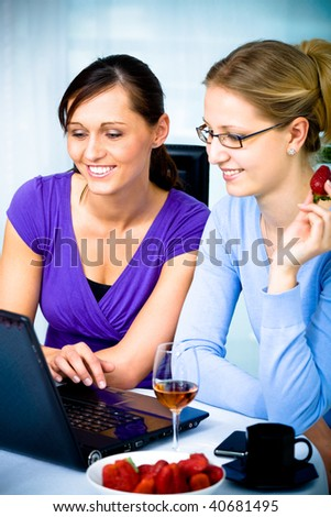 two young woman surfing internet in cafe