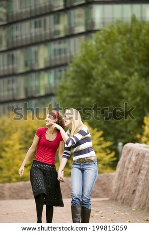 Two young woman walking, pointing - stock photo