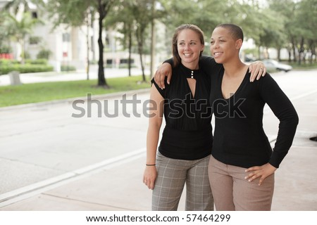 Two young woman with arms around each others shoulders - stock photo