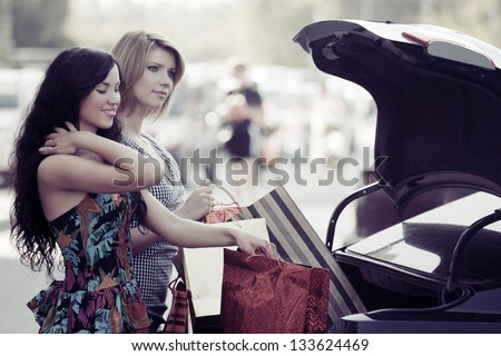 Two young woman with shopping bags on a car parking - stock photo