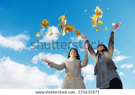 two young woman with throwing up autumn maple leaves in park at fall outdoors - stock photo