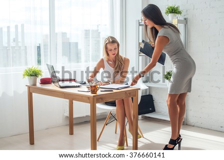 Two young woman working together in office. Subordinate and boss. - stock photo