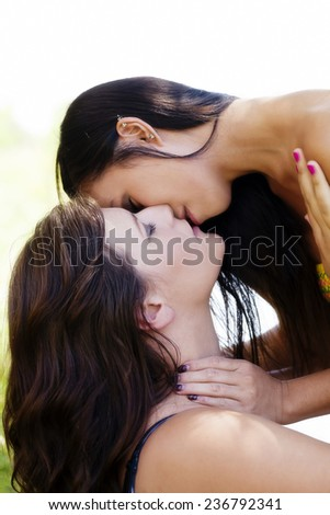 Two Young Women About To Kiss Outdoors