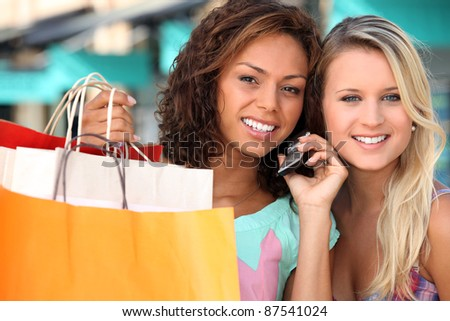 two young women after shopping, one is calling someone - stock photo