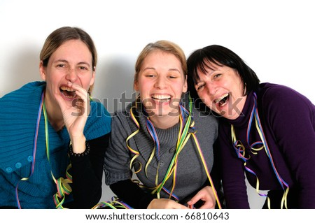 Two young women and one senior woman laughing at party.