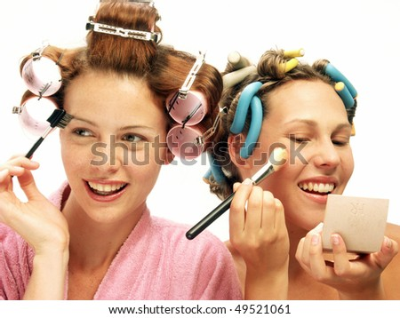 Two young women applying makeup mirror. - stock photo