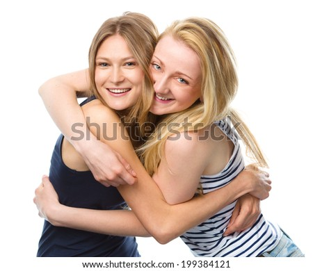 Two young women are hugging as a best friends, isolated over white