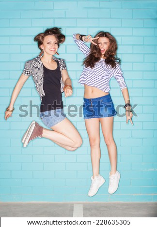 two young women are jumping against blue wall. Lifestyle - stock photo