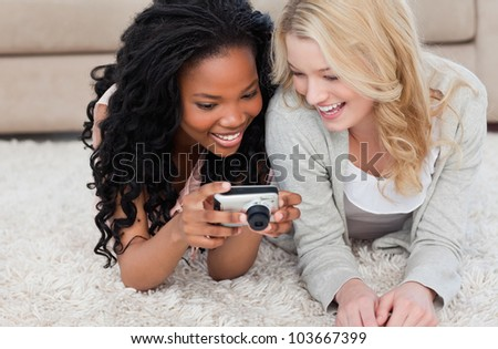 Two young women are lying on the floor at looking at photos on a digital camera - stock photo