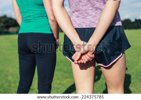 Two young women are wearing sportswear in the park on a sunny day - stock photo