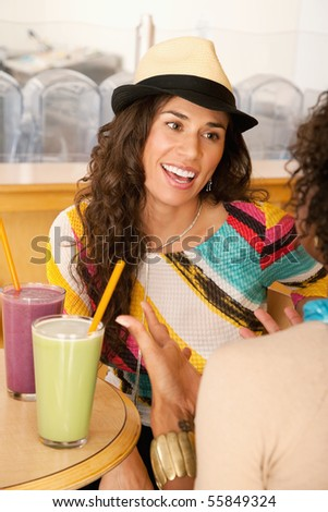 Two young women at a cafe drinking frozen beverages. Vertical shot. - stock photo