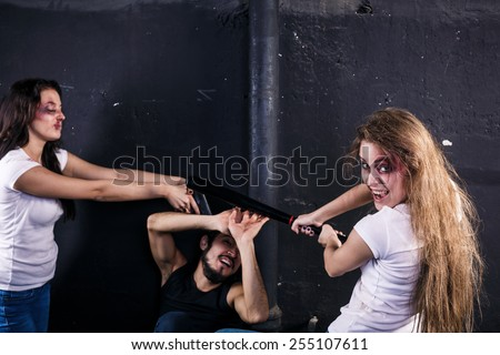 Two young women beating and shooting man  - stock photo