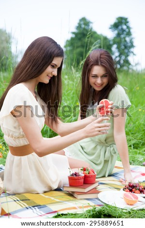 Two young women - best friends at a picnic, enjoying the good weather, making fresh juice and having fun. - stock photo