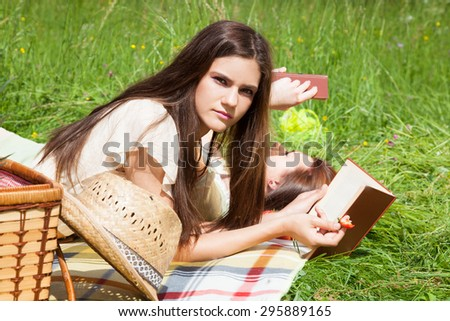 Two young women - best friends at a picnic, lying on grass and reading books. - stock photo