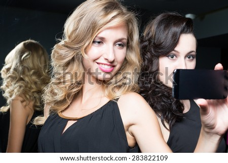 Two young women - best friends celebrating and taking a picture of themselves.  - stock photo