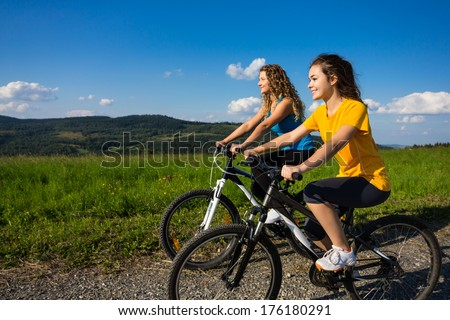 Two young women biking  - stock photo