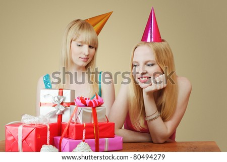 Two young women celebrating birthday. Looking at heap of gift boxes - stock photo