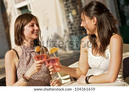 Two Young Women Cheering with Cold Drinks,Italy
