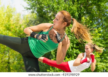 Two young women demonstrating side kicks in taebo training - stock photo