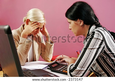 two young women discuss over some paperwork-on pink - stock photo