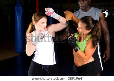 Two young women doing some light sparring and throwing elbows while their trainer looks on - stock photo