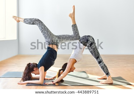 Two young women doing yoga asana downward facing dog. Adho Mukha Svanasana - stock photo