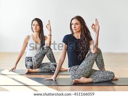 Two young women doing yoga asana half lord of the fishes pose. Ardha Matsyendrasana - stock photo
