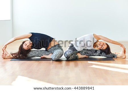 Two young women doing yoga asana revolved head to knee pose. Parivrtta Janu Sirsasana - stock photo