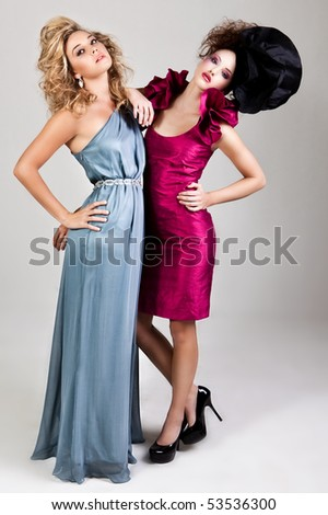 Two young women dressed in glamorous, avant garde attire. Vertical shot.