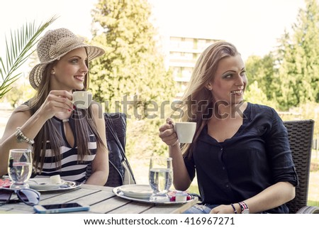 Two young women drinking a coffee in the city at summer.