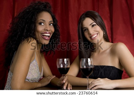 Two young women drinking at a night club - stock photo