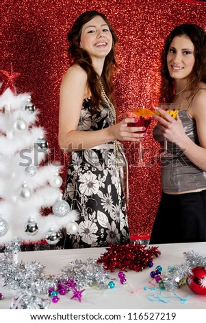 Two young women drinking cocktails and having fun with a christmas tree and a red glitter background. - stock photo