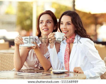 Two young women drinking coffee in a cafe - stock photo