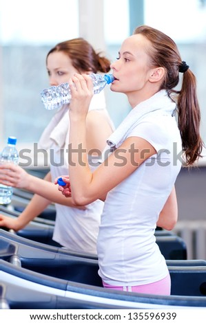 Two young women drinking water after sports. Fitness gym. - stock photo