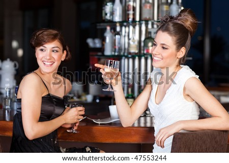Two young women drinking water at bar - stock photo