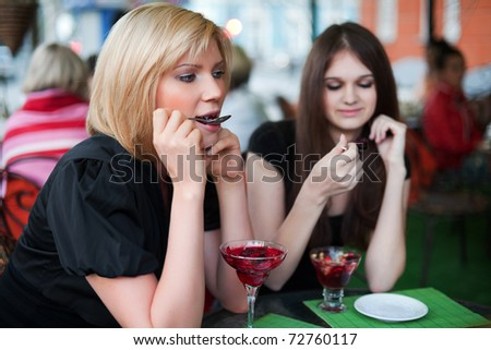 Two young women eating a dessert at sidewalk cafe - stock photo