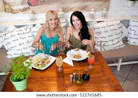 Two young women eating lunch. Healthy eating. Fresh food. Italian traditional dish.