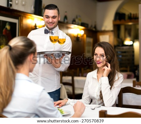 Two young women eating salads and drinking wine in a rural restaurant - stock photo
