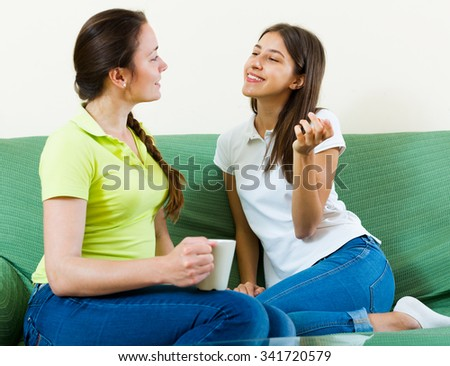 Two young women enjoying a conversation in a living room at the home  - stock photo
