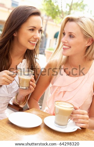Two Young Women Enjoying Cup Of Coffee In Cafe - stock photo