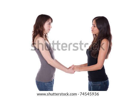 Two young women, facing each other, holding hands. - stock photo