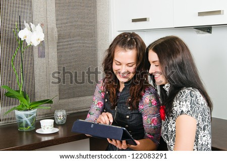 Two young women friends chatting at home and using laptop to look at new photo or browsing internet for information