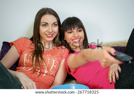 Two young women friends watching tv and sitting comfortable on couch in a living room.