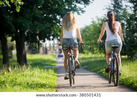 Two young women girlfriends wearing jeans shorts biking on sidewalk in park on sunny summer day, back view