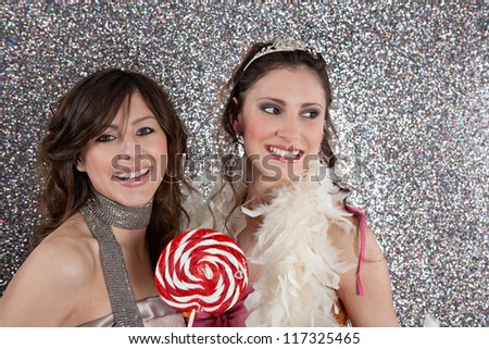 Two young women having a party and eating candy against a silver glitter background. - stock photo