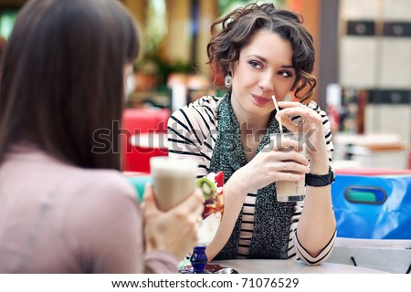Two young women having coffee break together - stock photo