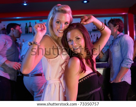 Two Young Women Having Fun In Busy Bar - stock photo