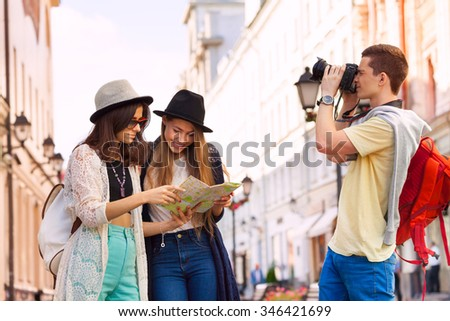 Two young women hold city map and guy with camera