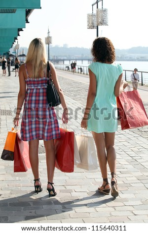 two young women holding carton bags and walking on a wharf - stock photo