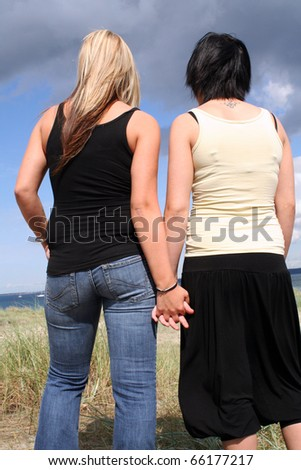 Two young women holding eachother at the beach